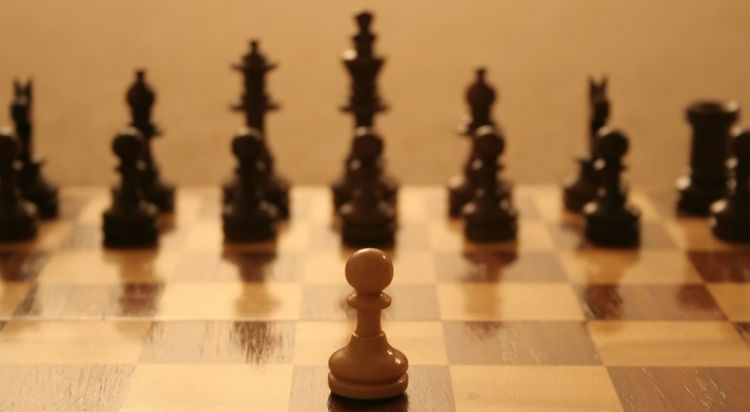 A Chess Pawn Infront Of A Chess Set