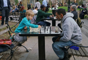 A Kid Playing Chess Against an Adult In New York