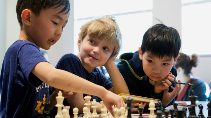 3 Kids Playing Chess In School