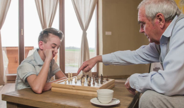 A Kid And A Senior Playing Chess