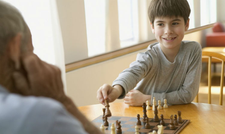 A Kid Plays Chess With An Adult