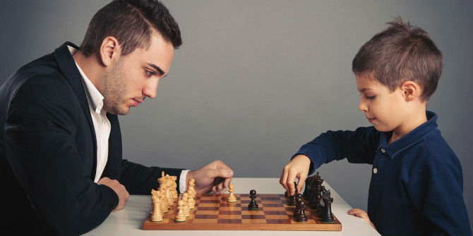 A Child & An Adult Playing Chess