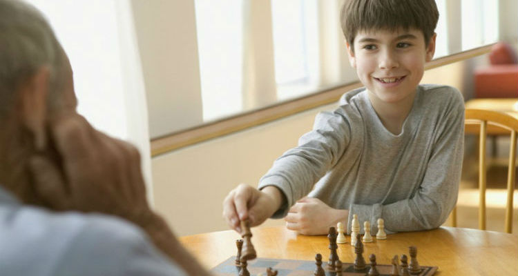 Chess game between a chess coach and a happy student