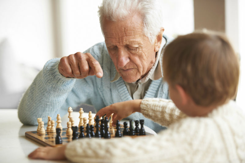 Elderly Man Teaches Grandson About Chess