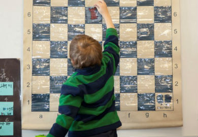 Kid Solving a Chess Problem During a First Move Chess Lesson