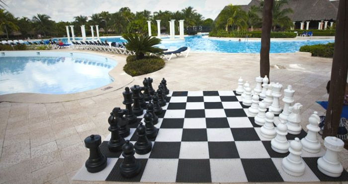The Rolly Toys Giant Chess Set Next To A Swimming Pool