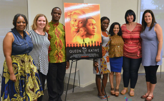 Robert Katende and Phiona Mutesi nexxt to a poster of the Queek of Katwe movie