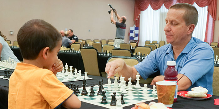A man and a kid playing chess at the Open Play Chess event of the Sunrise Center for Excellence in Chess