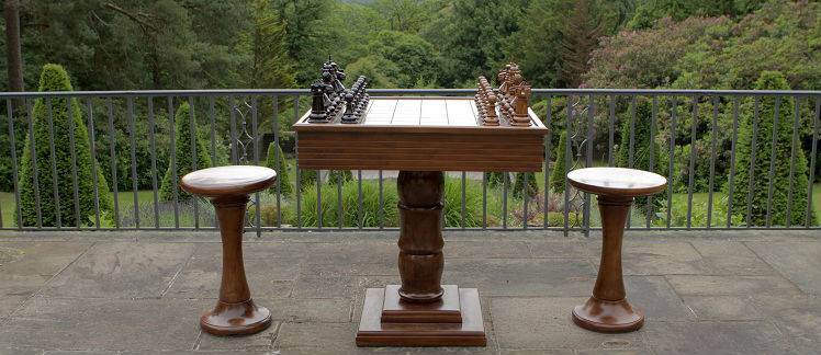 A Wooden Chess Table With Stools and Chess Pieces With forest View